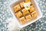 Toasted Mallows in square white bowl, sitting on terazzo background with shredded coconut scattered nearby.