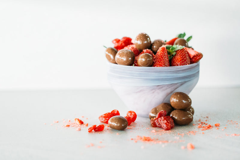 Milk Chocolate Strawberries in bowl with fresh strawberries, on light grey background.