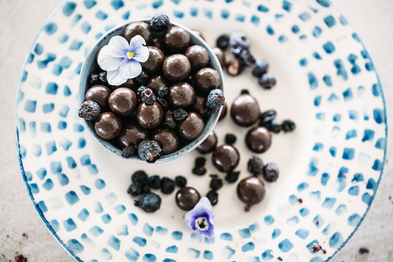 Small bowl of Dark Chocolate Blueberries stacked on white and blue plate. Decorated with purple edible flowers.