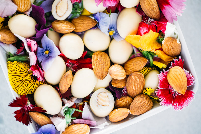 Yoghurt Coated Almonds scattered in bowl of brightly coloured edible flowers.