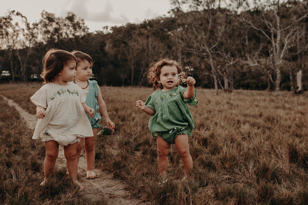 three little girls looking at flowers in nature