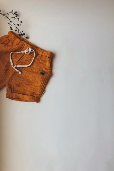 orange boy and girl shorts with side pockets and bee embroidery