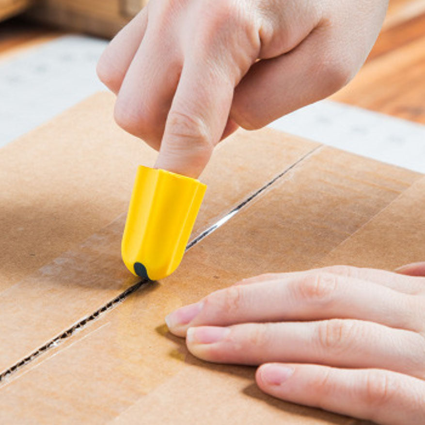 image of finger Safety cutter cutting a package tape