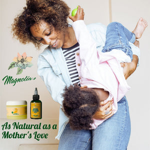 Women holding child Magnolia's scalp treatment hair beard & skin oil captioned  As natural as a mothers love