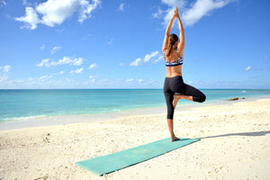 Woman in yoga outfit stands strong in tree pose, arms to the blue sky, on her Whale Song Yoga mat. She is surrounded by the clearest turquoise water and white sand.