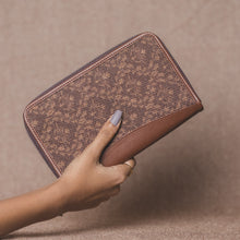 Load image into Gallery viewer, Zouk Brown Floral Motif Chain Wallet - Model holding the wallet in hand view