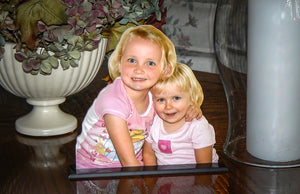 Two young girls as a photo statuette sitting on a coffee table.