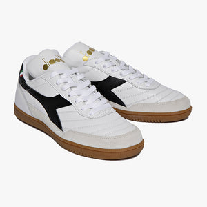 white leather with suede hits around toe black diadora logo with gum sole