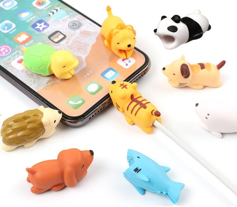 A set of cute animal bite cable charging cord protectors beside and on top of an iPhone
