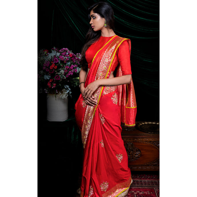 Banarasi Sari in Fiesta Red with artisanal hand-embroidery which speaks of pure beauty and traditional sentiments.