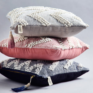 Stack of handmade ethical cushions in wave Aalto design