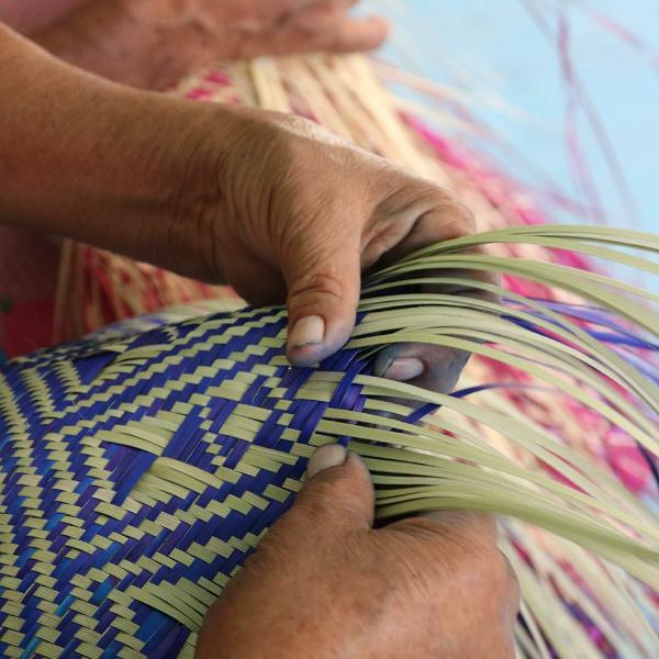 Mexican artisan hand weaving palm leaves into a basket