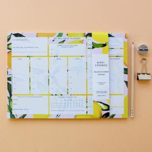 citrus lemon A4 wellness planner next to some stationary