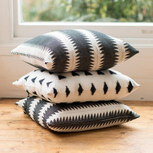 Lifestyle shot of handmade ethical cushion with global stripe design and tassel