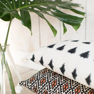 Lifestyle shot of handmade ethical cushion with ikat design and tassels