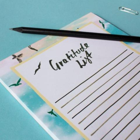 Close up of Gratitude list notepad lifestyle shot next to some stationary