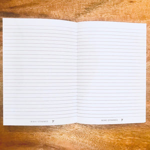 Inside of notebook showing lines and nikki strange logo on bottom of each page