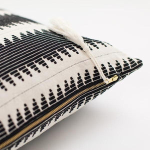Close up of handmade ethical cushion with global stripe design and tassel