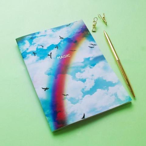 Magic Rainbow Haze notebook styled next to stationary