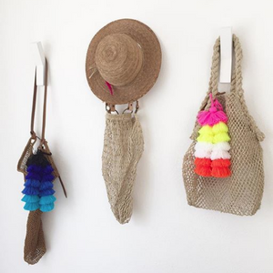 Different coloured pompoms on bags which are hanging off the wall