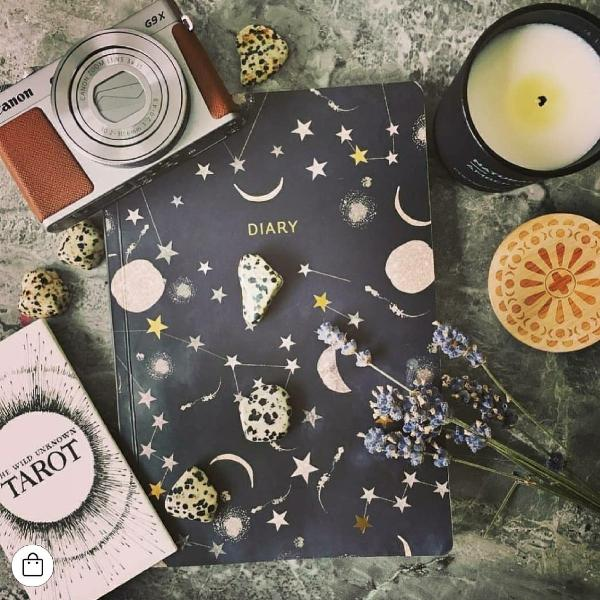 Constellation diary lifestyle shot with candles and crystals
