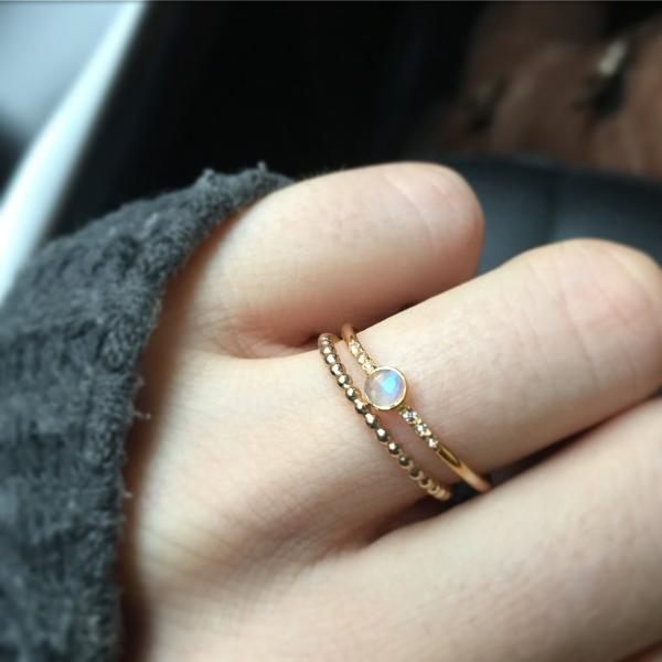Lifestyle shot of Rainbow Moonstone and Topaz Galaxy Ring stacked on finger with other rings