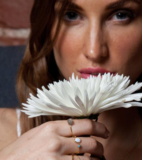 Lifestyle shot of woman holding white flower with dual ring on her hand