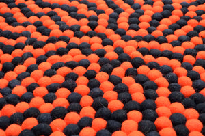 Round Black And Orange Felt Ball Rug