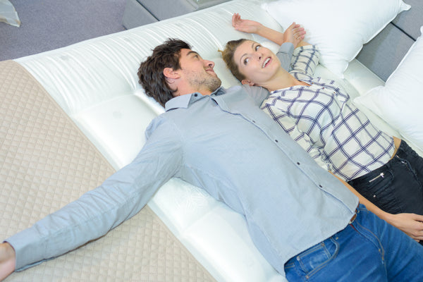 Couple laying on top of mattress