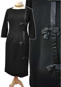 vintage black wool cocktail dress with black satin bows along the front and bracelet length sleeves by Brenner, made in England.