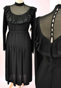 Chiffon sheer black 1970s cocktail dress with deep frill and illusion neckline, buttons down the back