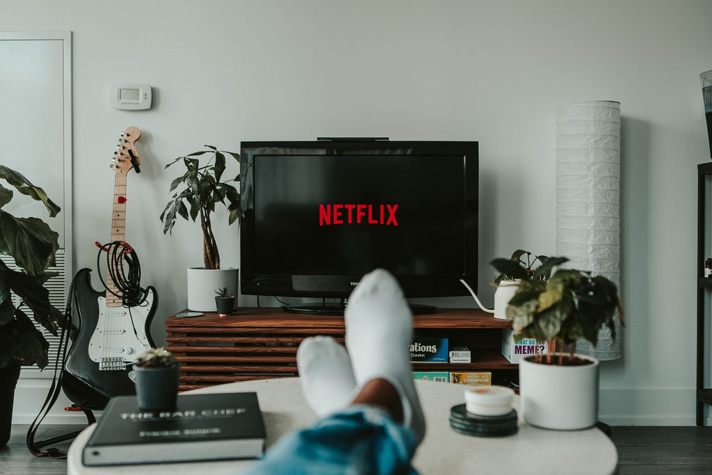 Person sitting down with their feet on a coffee table watching Netflix.