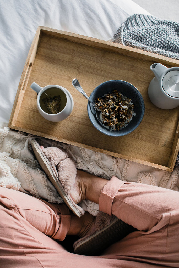 Person sitting on a bed with a tray with tea and snacks.