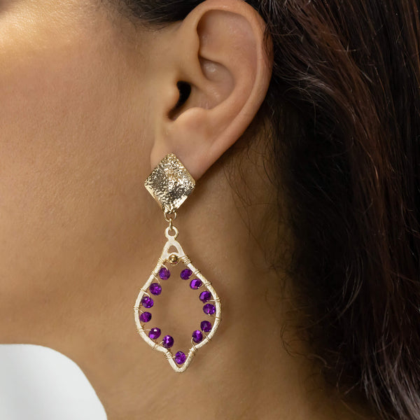 Chaima Earrings on a model. Gold Color Earrings with Purple Crystal Beads. Metal Frame & Wire Wrapped Earrings