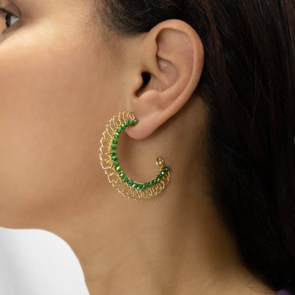 Bari Hoop Earrings on a model. Gold Color Earrings with Green Crystal Beads Wire Wrapped Hoop Earrings.