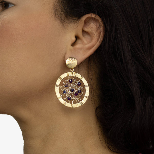 Janya Earrings on a model. Gold Color Wire Wrapped Earrings. Stud Earrings with Metallic Purple Crystal Beads Accent.