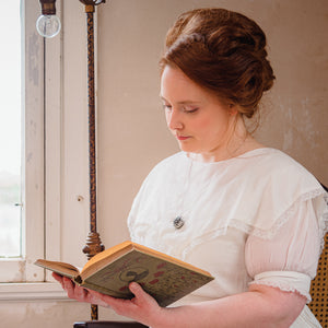 Anna of Willow & Birch Apothecary in a feminine and timeless victorian dress with a vintage style book