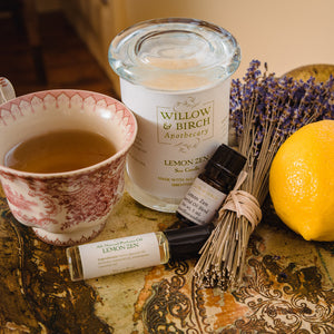 Lemon Zen scented natural bath, beauty, and fragrance products by Willow & Birch Apothecary pictured with antique teacup, fresh lemon, and lavender bouquet
