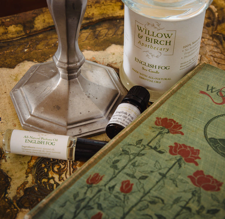 English Fog scented natural artisan bath, beauty, and fragrance products by Willow & Birch Apothecary pictured with antique candlestick and antique book, inspired by Downton Abbey and Jane Austen, vintage victorian style for old souls