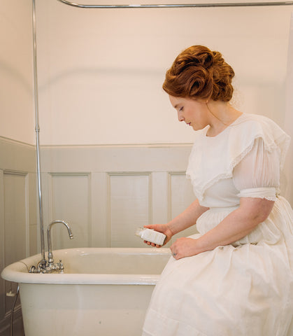 Victorian woman pouring Willow & Birch Apothecary bath salts into antique tub