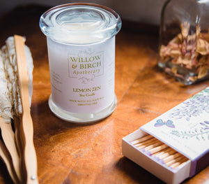 Scented soy candle by Willow & Birch Apothecary with apothecary jar of rose petals, Victorian style fan, and book of decorative matches