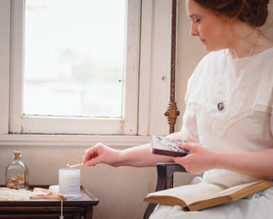 Woman in Victorian dress lighting a scented soy candle by Willow & Birch Apothecary while holding an antique book in front of a window