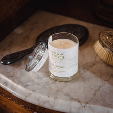 Scented soy candle by Willow & Birch Apothecary with antique mirror and brush on marble vanity