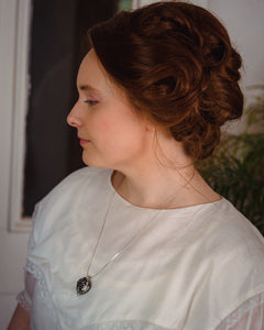 Woman in white Victorian dress wearing antique-style aromatherapy scent locket perfume locket by Willow & Birch Apothecary