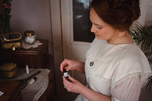 Woman in white Victorian dress wearing antique-style aromatherapy scent locket perfume locket by Willow & Birch Apothecary and holding essential oil blend while sitting at antique marble-topped vanity table