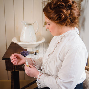 Woman in Victorian clothing applying perfume by Willow & Birch Apothecary