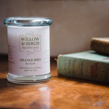 Scented soy candle by Willow & Birch Apothecary with a stack of antique books