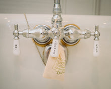 Lavender and Chamomile botanical bath tea epsom soak by Willow & Birch Apothecary on antique style bath tub with silver faucet handles