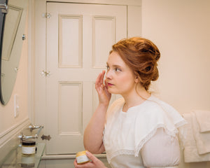 Woman in Victorian dress applying moisturizer face cream