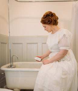 Woman in Victorian dress pouring bath salts by Willow & Birch Apothecary into antique clawfoot bath tub